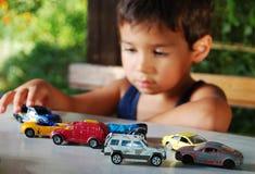 Niños que juegan con los juguetes de los coches al aire libre Fotografía de archivo libre de regalías