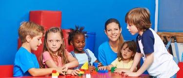 Niños que juegan con los ladrillos del edificio en cuidado de niños fotos de archivo