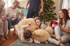 Niños que juegan con los regalos abiertos gigantes de Teddy Bear As Multi-Generation Family el día de la Navidad fotografía de archivo libre de regalías