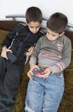 Niños que juegan con sus smartphones Foto de archivo libre de regalías