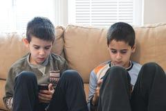 Niños que juegan con sus smartphones Fotos de archivo libres de regalías