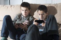 Niños que juegan con sus smartphones Imagen de archivo libre de regalías