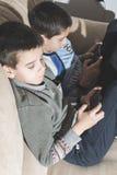 Niños que juegan con sus smartphones Imagenes de archivo