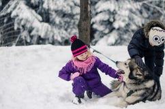 Niños que juegan con un perro Imagenes de archivo