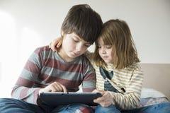Niños que juegan con una tableta digital Fotos de archivo
