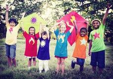 Niños que juegan concepto de la amistad de la vinculación de la felicidad de la cometa Imagenes de archivo