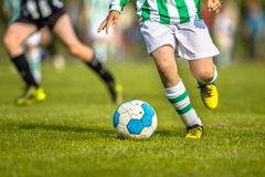 Niños que juegan deporte del fútbol en echada natural de la hierba Imágenes de archivo libres de regalías