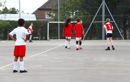 Niños que juegan deportes en patio imagen de archivo