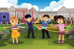 Niños que juegan el aro del hula en el parque Imagen de archivo