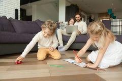 Niños que juegan el dibujo en casa, toget del tiempo libre del gasto de la familia Foto de archivo libre de regalías
