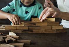 Niños que juegan el juguete de madera del bloque con el profesor Imagen de archivo libre de regalías