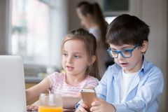 Niños que juegan el ordenador y el smartphone mientras que desayuno de cocinar ocupado de la madre fotografía de archivo libre de regalías