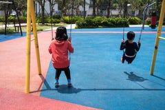 Niños que juegan el oscilación en patio Juego de los niños al aire libre el día soleado Imagenes de archivo
