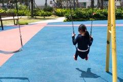 Niños que juegan el oscilación en patio Juego de los niños al aire libre el día soleado Imágenes de archivo libres de regalías