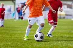 Niños que juegan el partido de fútbol del fútbol Jugadores corrientes y retroceso Imagen de archivo libre de regalías