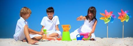 Niños que juegan en arena de la playa Foto de archivo libre de regalías