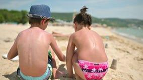 Niños que juegan en arena en la playa metrajes