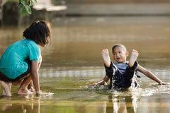 Niños que juegan en cuadrado inundado Fotos de archivo libres de regalías