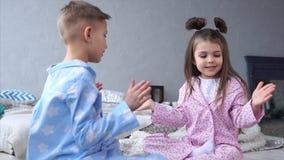 Niños que juegan en dormitorio Niña y muchacho que se sientan en cama metrajes