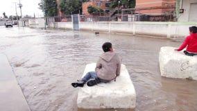 Niños que juegan en el agua durante la inundación