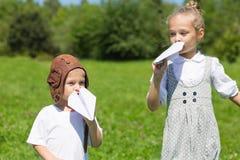 Niños que juegan en el avión de papel al aire libre Foto de archivo libre de regalías