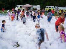 Niños que juegan en el bombero Foam Imagen de archivo libre de regalías
