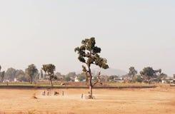 Niños que juegan en el campo del grillo Paisaje en la India Foto de archivo