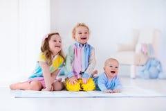 Niños que juegan en el dormitorio blanco Fotos de archivo libres de regalías