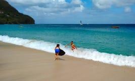 Niños que juegan en el mar del Caribe fotos de archivo libres de regalías