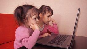 Niños que juegan en el ordenador portátil Imprimen a dos niñas en un ordenador portátil Dos hermanas que se sientan en el sofá an metrajes