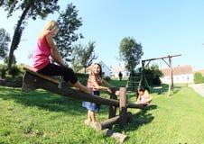 Niños que juegan en el oscilación de madera Imagen de archivo libre de regalías