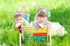 Niños que juegan en el parque - los niños aprenden la cuenta al aire libre Imagen de archivo libre de regalías