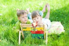 Niños que juegan en el parque - los niños aprenden la cuenta al aire libre Foto de archivo libre de regalías