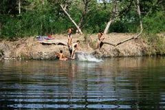 Niños que juegan en el río Fotos de archivo