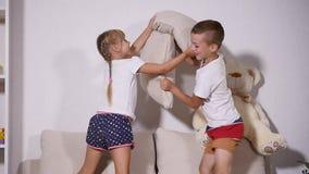Niños que juegan en el sofá con los pilows, cámara lenta