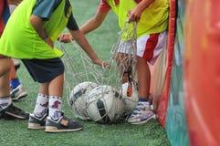 Niños que juegan en escuela del fútbol del fútbol con el instructor Foto de archivo