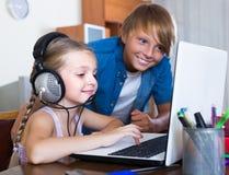 Niños que juegan en línea en el ordenador portátil Imagenes de archivo