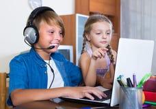 Niños que juegan en línea en el ordenador portátil Fotografía de archivo