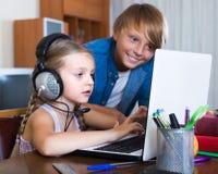 Niños que juegan en línea en el ordenador portátil Fotografía de archivo libre de regalías