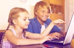 Niños que juegan en línea en el ordenador portátil Foto de archivo libre de regalías