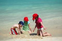 Niños que juegan en la arena Imagen de archivo libre de regalías