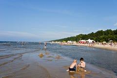 Niños que juegan en la arena en el mar. Fotos de archivo libres de regalías