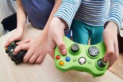 Niños que juegan en la consola de los juegos fotografía de archivo libre de regalías