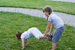 Niños que juegan en la hierba Imagenes de archivo