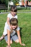 Niños que juegan en la hierba Foto de archivo libre de regalías