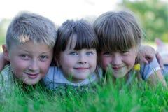 Niños que juegan en la hierba fotos de archivo