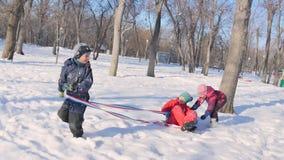 Niños que juegan en la nieve en invierno almacen de metraje de vídeo