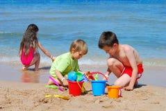 niños que juegan en la playa fotos de archivo