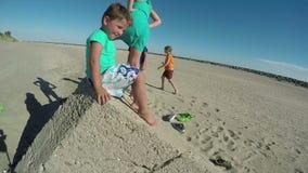 Niños que juegan en la playa cerca de una piedra grande almacen de metraje de vídeo