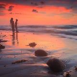 Niños que juegan por la playa en la puesta del sol Fotografía de archivo libre de regalías